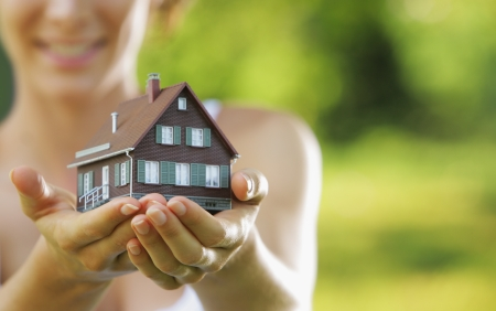 house in hand: Young beautiful woman offering a house
