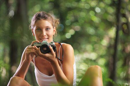 ojos verdes: Mujer hermosa en el bosque con la cámara de la vendimia