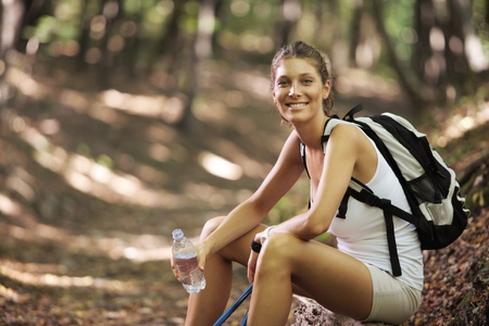 15147384: Smiling woman with walking sticks in a forest, having a break Stock Photo