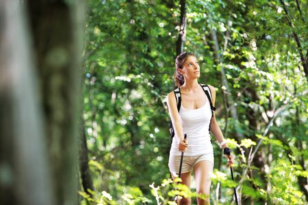 nordic walking: Woman walking cross country in a green forest Stock Photo