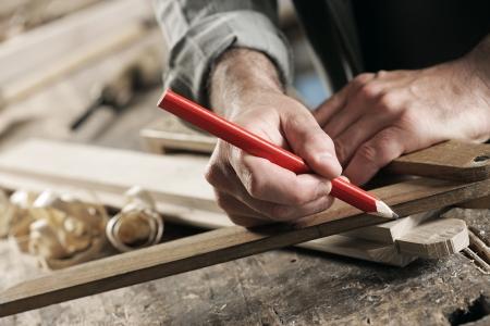 carpintero: Cierre de vista de un carpintero utilizando una regla para dibujar una l�nea en un tablero. Foto de archivo