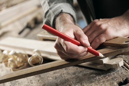 Close Up view of a carpenter using a straightedge to draw a line on a board. Stock Photo - 15284802
