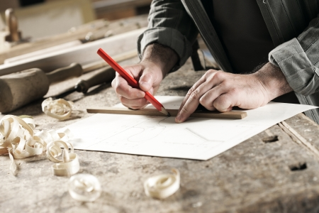 wooden pencil: Closeup  view of a carpenter using a red pencil to draw a line on a blueprint