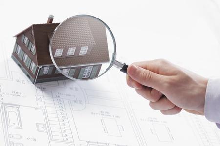 Concept beeld van een huis inspectie. Een mannelijke hand houdt een vergrootglas over een miniatuur huis.