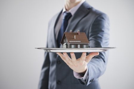 Real estate offer. Businessman holding a silver tray with an artificial model of the house photo