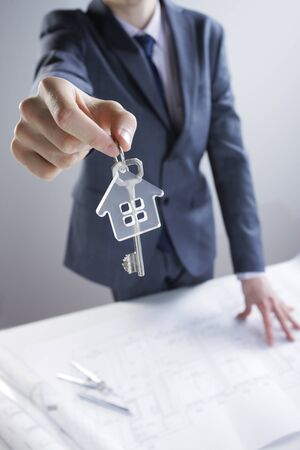 hands out: Young businessman giving house keys