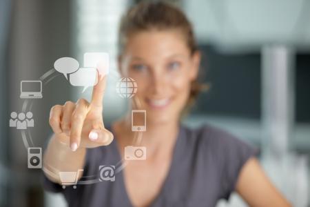 �cran tactile: Sourire, femme appuyant sur l'�cran tactile sur l'ic�ne de r�seau social