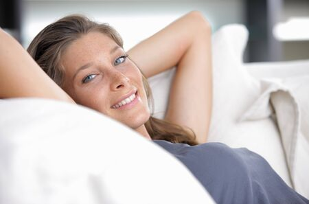 buen vivir: Primer plano de una mujer joven y sonriente acostado en el sofá