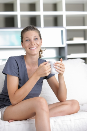 Portrait of a cute young lady sitting on sofa with a cup of coffee Stock Photo - 15261625