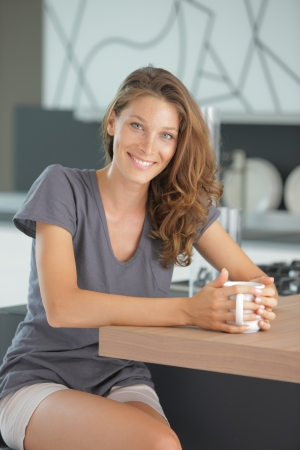 Beautiful girl in kitchen with a cup of cofee or tea photo