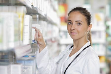 pharmacist: Portrait of a young female pharmacist selecting a medication
