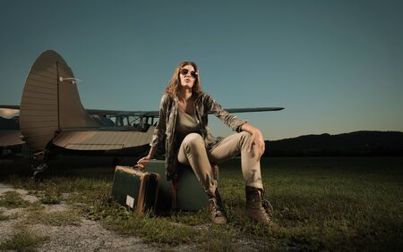Fashion  woman with a suitcase, ready to start. Airplane in the background. photo