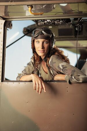 Portrait of young woman pilot in a military airplane. Copy space photo