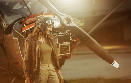 pilots: Portrait of beautiful woman aviator in airport at sunset Stock Photo