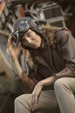Portrait of young woman airplane pilot. Airplane on the background photo