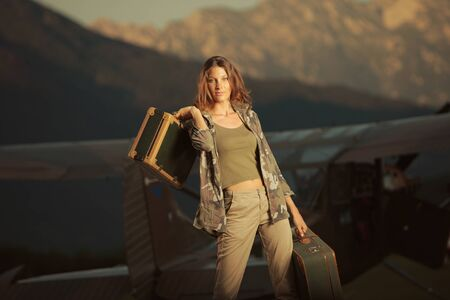 Young beautiful woman with suitcases ready to go by plane at sunset photo