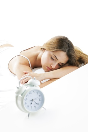 A young lady sleeping on the background with a clock on the foreground. Stock Photo - 15517665