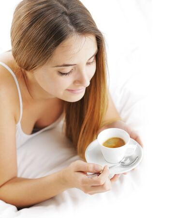 Beautiful young woman in bed drinking cofee in the morning. Stock Photo - 15517681