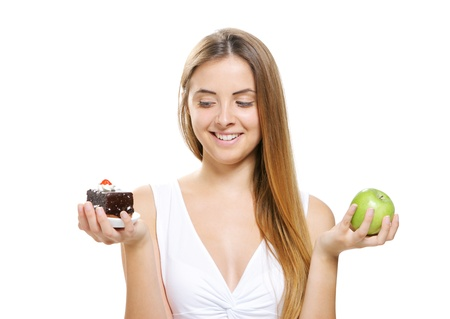 diet concept:  Woman choosing between fruits and cakes photo