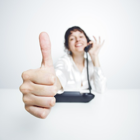thumbs up shown by a happy, smiling young woman working at her office desk while phoning photo