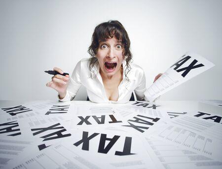 impuestos: Joven mujer asustada gritando mientras est� sentado en su escritorio cubierto de papeles con un marcador en una mano y una factura de impuestos en el otro