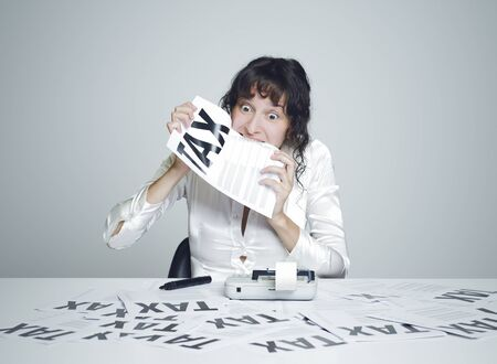 Young desperate woman at her paperwork covered desk biting a tax form Stock Photo - 15517684
