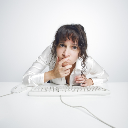 Funny and quite grotesque frontal portrait of a doubtful woman at her office desk Stock Photo - 15517661