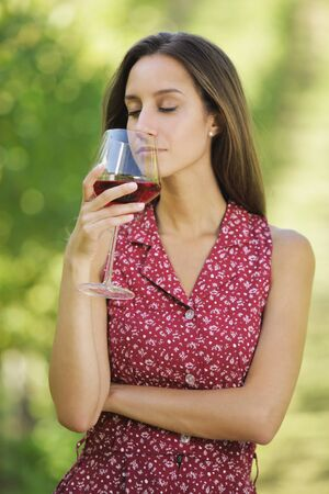 Vintner woman check red wine in a vineyard photo