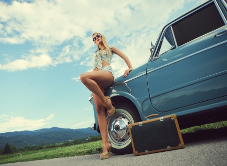 roadside stand: Fashion model with vintage cars, cloudy sky on background Stock Photo