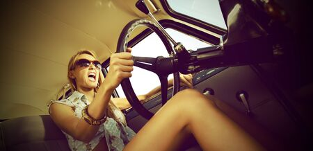 Beautiful young woman driving vintage car. photo