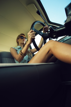 unusual angle: Beautiful young woman driving vintage car.