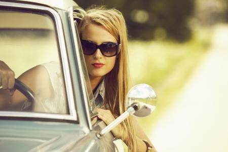 manejando: Mujer joven que conduce el coche de �poca. Foto de archivo