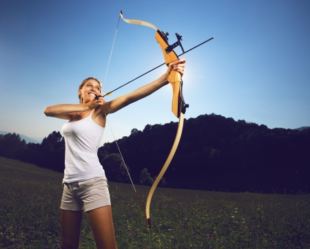 archery target: Attractive female archer bending a bow and aiming in the sky Stock Photo