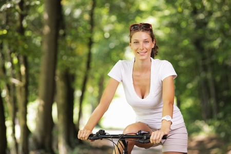 mountain bicycles: Young woman on a bicycle in the forest