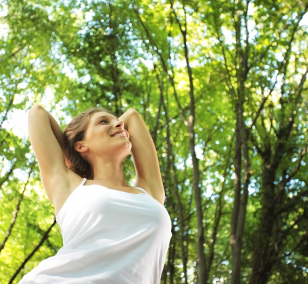 arms  outstretched: Beautiful woman enjoying the nature in green forest Stock Photo