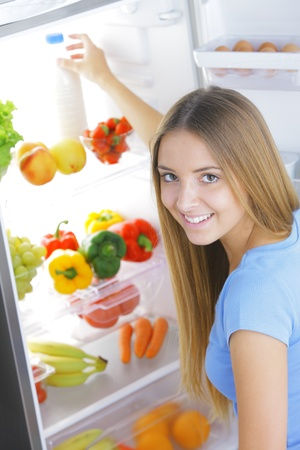refrigerator with food: Young woman takes a bottle of milk