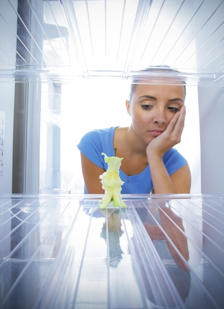 Young woman unhappy to see the empty fridge Stock Photo - 15471770