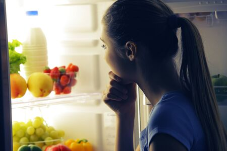 diet woman: Young woman craving food choosing near refrigerator at night