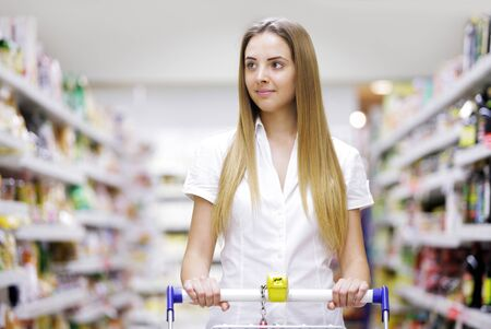 food store: Young beautiful woman with shopping cart Stock Photo