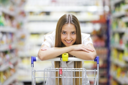 Happy blonde shopper smiles over supermarket shopping cart photo