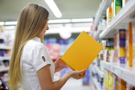 labelling: Woman checking food labelling in supermarket