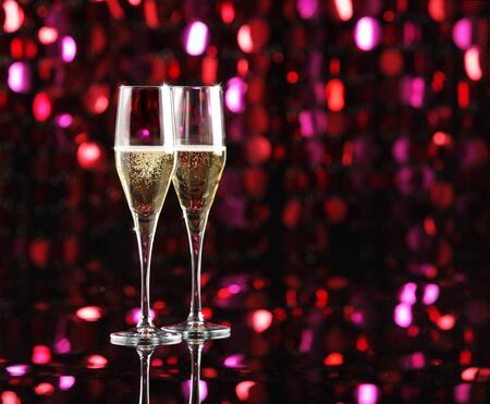 new year  s day: Two glasses of champagne, colored lights as background