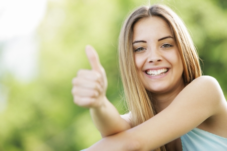 real people: Young smiling blond female outdoors showing thumb up sign