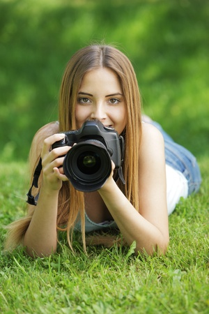 Young woman making photos at summer green park. photo