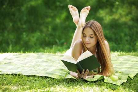 woman reading book: Closeup of a beautiful young woman reading book at park