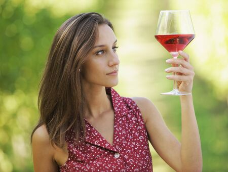 french culture: Vintner woman check red wine in a vineyard