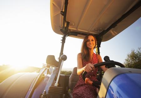 Junge Frau einen Traktor zu fahren bei Sonnenuntergang Standard-Bild