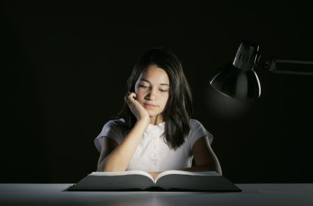 Young girl student, studying late into the night with her book and homework  photo
