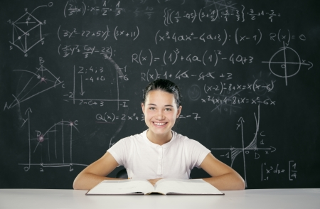 Student sitting in front of a blackboard full of math formulas photo