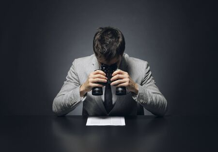 myopic: Young businessman looking to a document through a binoculars Stock Photo